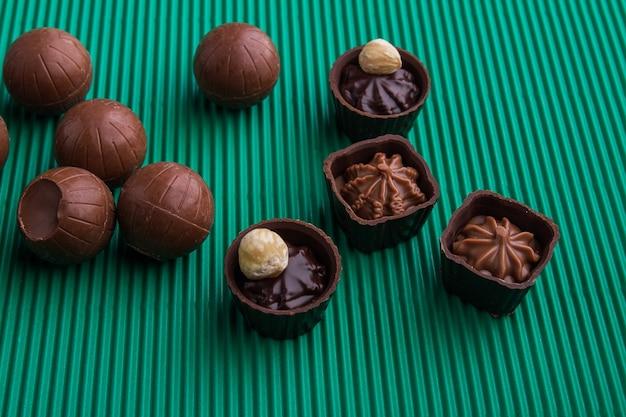 Variedade de vários bombons de chocolate doces com diferentes recheios. fundo verde listrado.