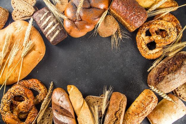 Variedade de vários deliciosos pães recém-assados, no fundo de concreto preto, vista de cima, espaço de cópia