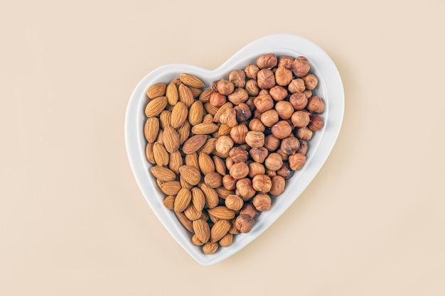 Variedade de vários tipos de nozes - avelãs, amêndoas no prato em forma de coração no fundo pastel.