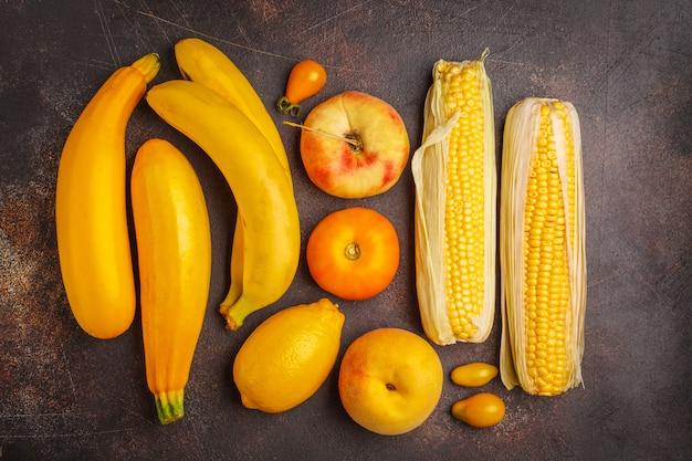 Variedade de vegetais amarelos em fundo escuro, vista superior. frutas e vegetais contendo caroteno.