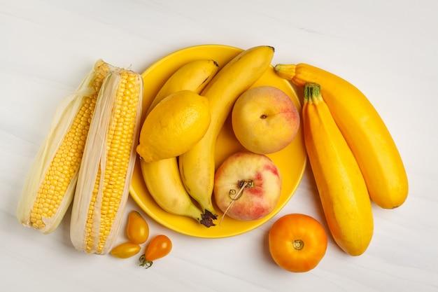 Variedade de vegetais amarelos no fundo branco, vista superior. frutas e vegetais contendo caroteno.