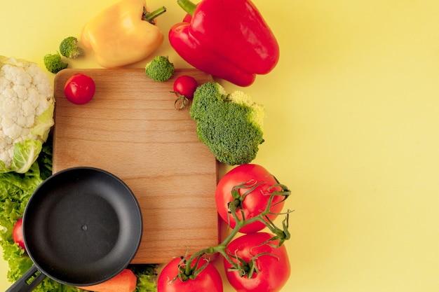 Variedade de vegetais e frigideira em um quadro negro