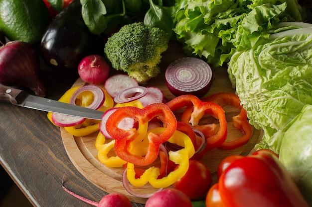 Variedade de vegetais e pimentão picado e cebola roxa em um conceito de cozinha de tabuleiro Foto Premium
