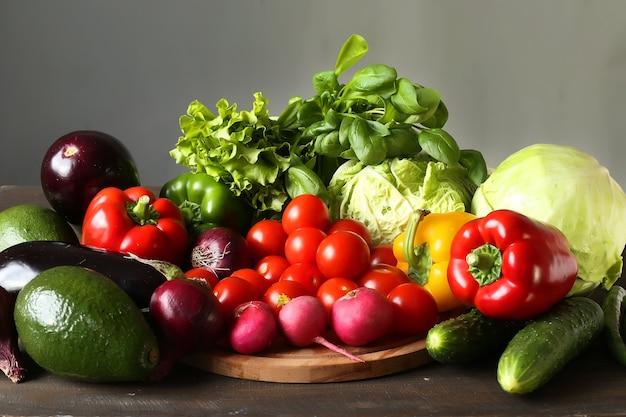 Variedade de vegetais frescos pimenta, rabanete, abacate, brócolis, berinjela, repolho, tomate, cebola roxa em uma placa
