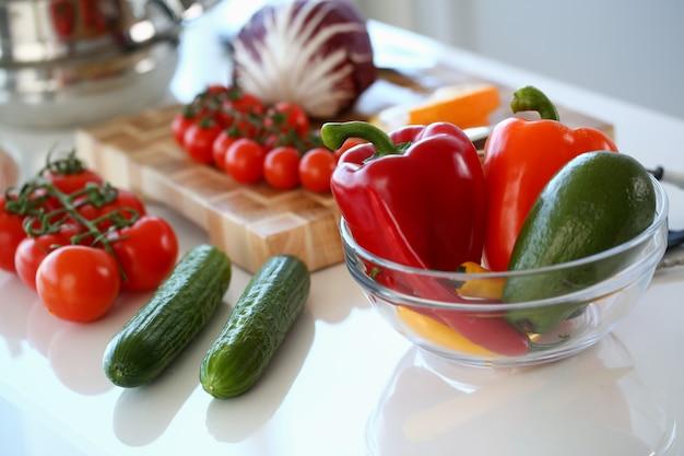Variedade de vegetais orgânicos vermelhos. pimenta, pimenta e tomate na bancada da cozinha.