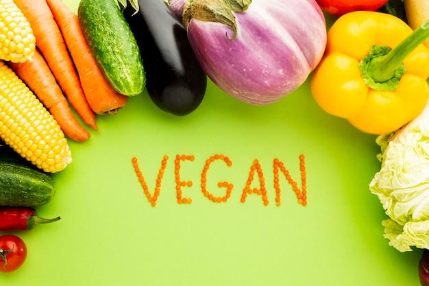 Variedade de vegetais sobre fundo verde com letras vegan
