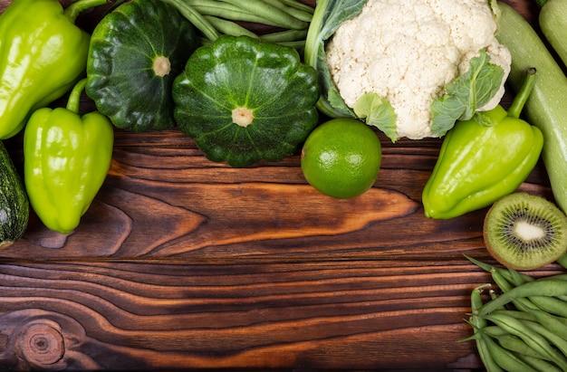 Variedade de vegetais verdes crus como moldura sobre fundo de textura escura