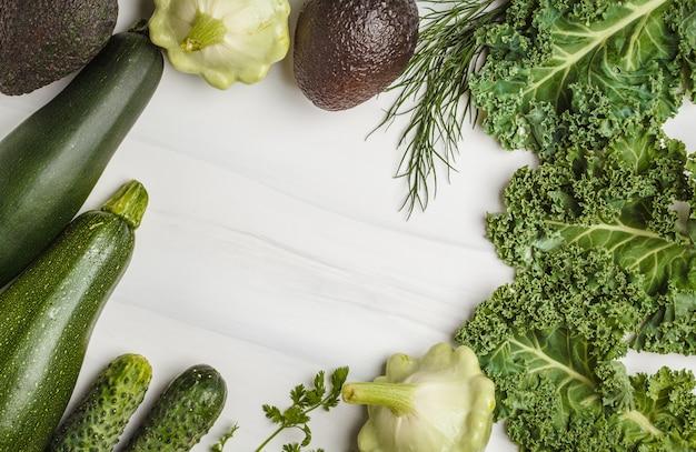 Variedade de vegetais verdes no fundo branco, vista superior. frutas e vegetais contendo clorofila.