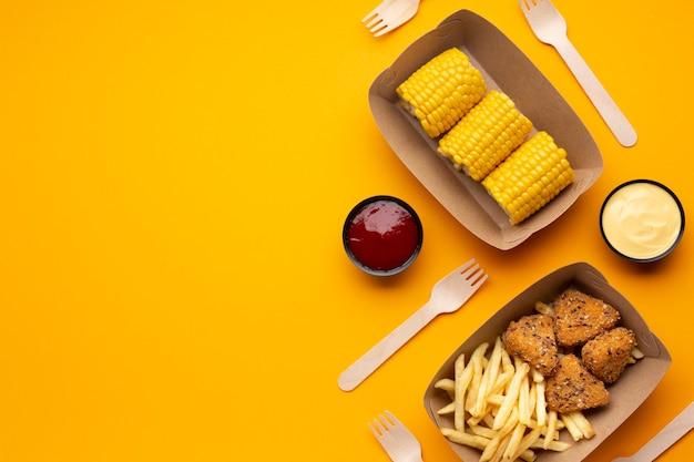 Variedade de vista superior com batatas fritas, crocante e milho