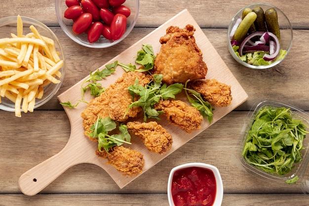 Variedade de vista superior com comida de frango e salada