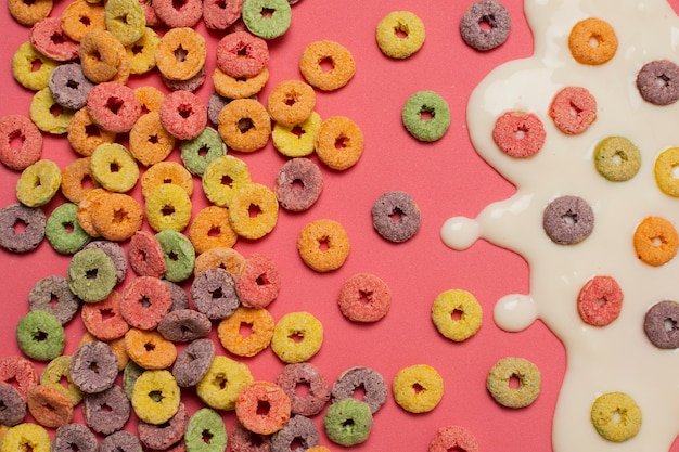 Variedade de vista superior com leite e cereais em fundo rosa