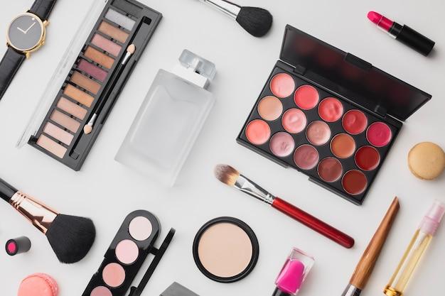 Variedade de vista superior com paleta de maquiagem e perfume