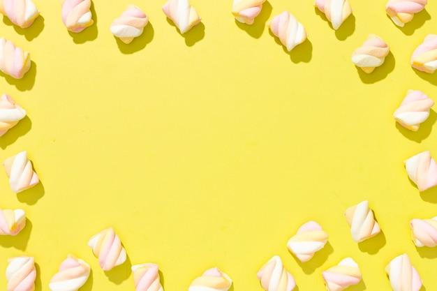 Variedade de vista superior de doces coloridos sobre fundo amarelo, com espaço de cópia