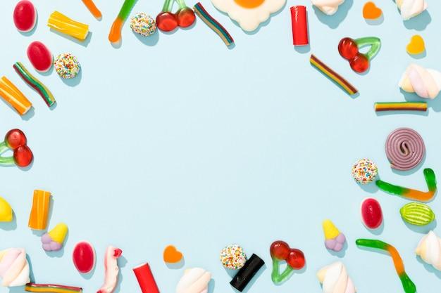 Variedade de vista superior de doces coloridos sobre fundo azul, com espaço de cópia