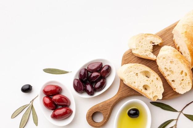 Variedade de vista superior de fatias de pão de azeitonas e azeite com espaço de cópia