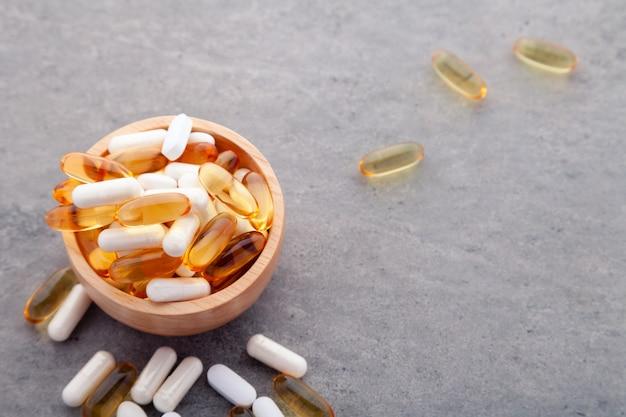 Variedade de vitaminas de medicamentos farmacêuticos, pílulas, cápsulas moles em uma tigela de madeira no fundo cinza
