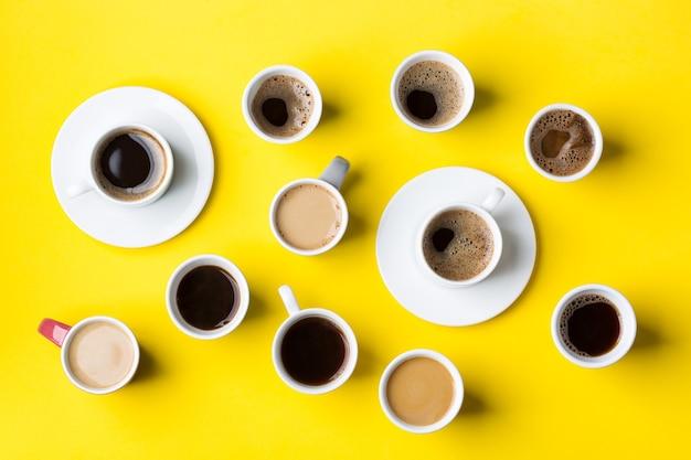 Variedade de xícaras de café e canecas com preto torrado, americano, cappuccino, leite sobre um fundo amarelo. criativo na moda plana lay