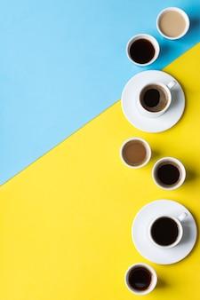 Variedade de xícaras de café e canecas com preto torrado, americano, cappuccino, leite sobre um fundo amarelo e azul. espaço criativo de cópia na moda plana lay