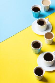 Variedade de xícaras de café e canecas com preto torrado, americano, cappuccino, leite sobre um fundo amarelo e azul. espaço criativo de cópia na moda