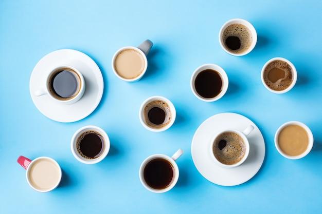 Variedade de xícaras de café e canecas com preto torrado, americano, cappuccino, leite sobre um fundo azul. criativo na moda plana lay