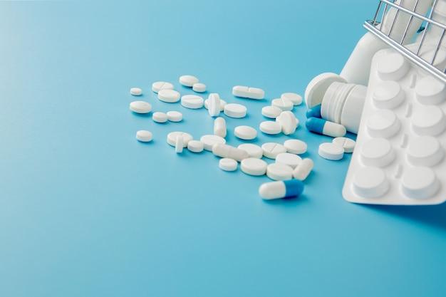 Variedade dispersa pílulas, drogas, esterilizar, garrafas, termômetro, seringa e carrinho de carrinho de compras vazio na mesa azul, conceito de compras de farmácia