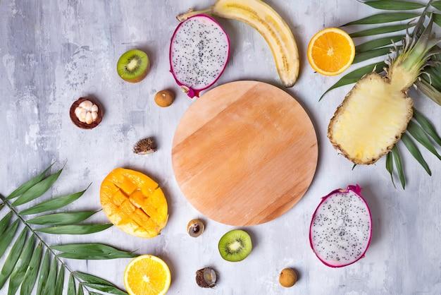 Variedade dos frutos tropicais com a placa de madeira para o espaço da cópia em um teste padrão claro de pedra do fundo. vista do topo.