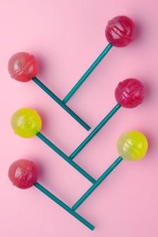 Variedade dos pirulitos no fundo pastel cor-de-rosa. um monte de pirulitos colorfull.