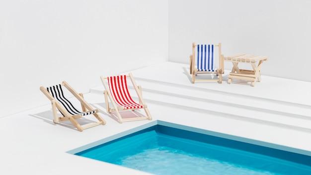 Variedade em miniatura de espreguiçadeiras ao lado da piscina