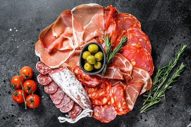 Variedade espanhola de carnes frias. chouriço, fuet, lombo, jamon ibérico, azeitonas. superfície preta. vista do topo.