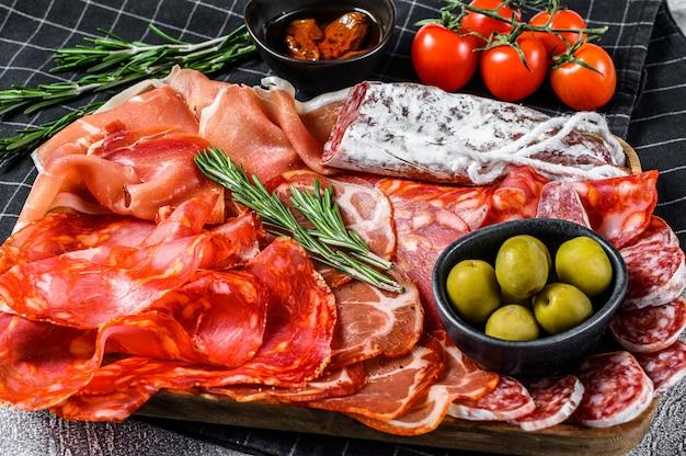 Variedade espanhola de carnes frias. chouriço, fuet, lomo, jamon ibérico, azeitonas. vista do topo