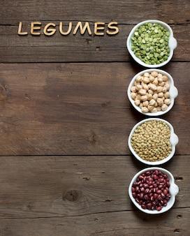 Variedade ou leguminosas e a palavra de leguminosas em uma vista superior de mesa de madeira marrom com espaço de cópia