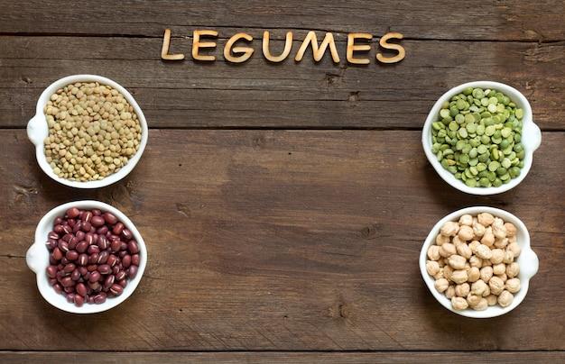 Variedade ou leguminosas em tigelas e a palavra leguminosas em uma vista superior de mesa de madeira marrom com espaço de cópia