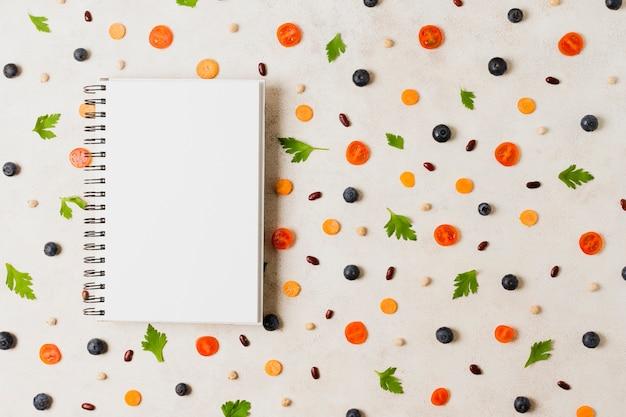 Variedade plana leiga com notebook e legumes