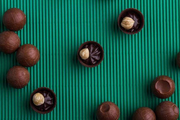 Variedade plana leiga da vista superior de bombons de chocolate doce. fundo verde listrado.