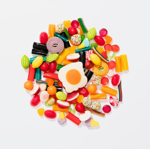 Variedade plana leiga de doces coloridos sobre fundo branco