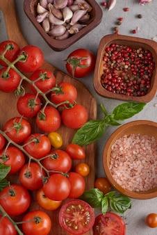 Variedade vermelha fresca de tomates com especiarias de manjericão, pimenta. conceito de tomate vegetal. comida de dieta vegana. colheita de tomates.