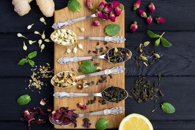 Variedades de chá nas colheres de prata na tábua de cortar marrom