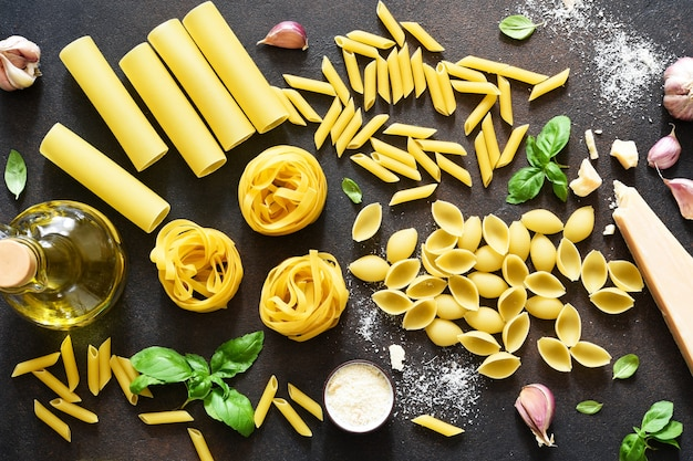 Variedades de massas. conjunto de macarrão com parmesão, azeite e manjericão em um fundo de concreto. vista de cima. ingredientes para fazer macarrão.