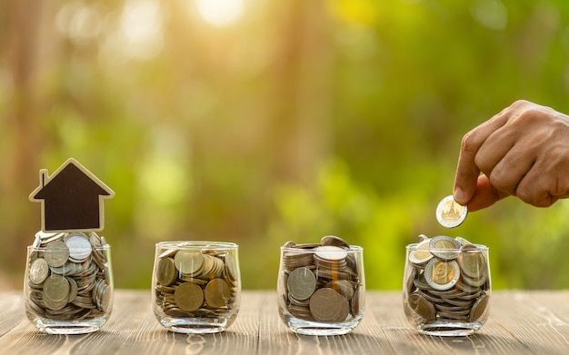 Varinha colocar a moeda no pote claro na mesa de madeira. economia de dinheiro para o conceito de casa