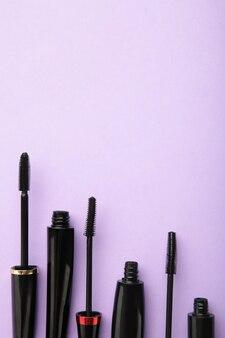 Varinha de rímel preta e tubo em fundo roxo com espaço de cópia. foto vertical. vista do topo
