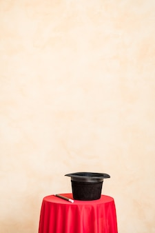 Varinha mágica e cartola preta na mesa contra a parede do grunge com espaço de cópia