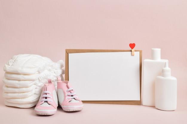 Vários acessórios para higiene infantil em um fundo rosa. uma grande pilha de fraldas ao lado deles - frascos de cosméticos para bebês. copie o espaço