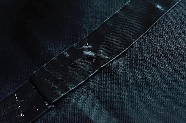 Vários alfinetes estão espalhados no pano preto. fechar-se.
