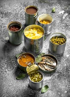 Vários alimentos enlatados com carne, peixe, vegetais e frutas em latas na mesa rústica.