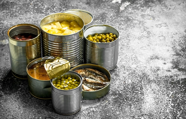 Vários alimentos enlatados com carne, peixe, vegetais e frutas em latas.