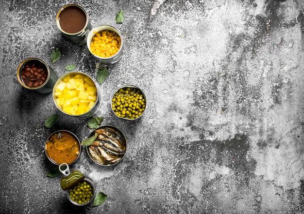 Vários alimentos enlatados com carne, peixe, vegetais e frutas em latas
