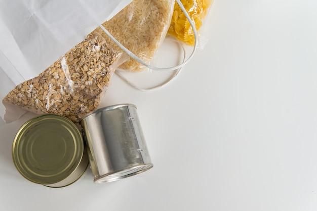 Vários alimentos enlatados, massas, arroz e grãos de cereais crus em uma mesa em saco de papel com espaço de cópia