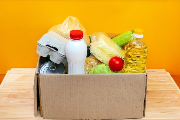 Vários alimentos enlatados, ovos e legumes em uma caixa de papelão.