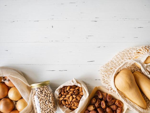 Vários alimentos frescos no pacote eco-amigável no fundo branco.