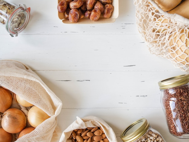 Vários alimentos frescos no quadro de pacote ecológico sobre fundo branco.